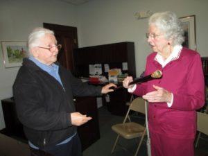 Lois Kenick, left, passes the Wilton Boston Post Cane to Kay Williams,.